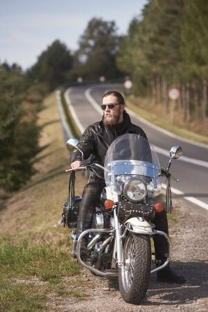 Handsome bearded biker with long hair in black leather jacket and sunglasses sitting on modern motorcycle on roadside, on blurred background of empty twisty road with white marking on sunny summer day Foto de archivo - 137436601