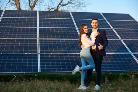Young and beautiful couple is standing close to each other by a solar panel, man shows thumb up, smiling at camera, full length, copy space Foto de archivo - 137589903