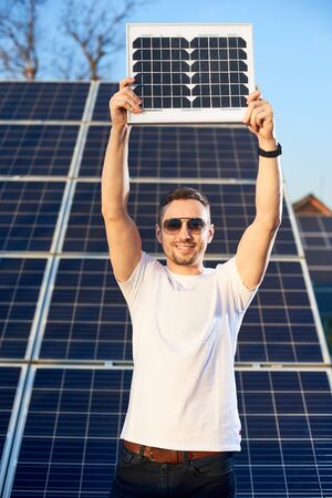 Smiling young man holding a small pv module above his head looking at the camera, solar plant behind his back, concept of alternative energy Foto de archivo - 137589905