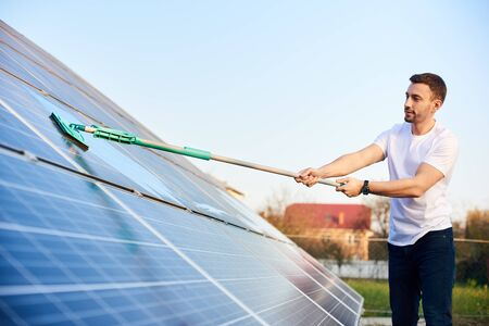 Young man is washing a solar panel with a mop, pv plant in rural area, cleaning increases to high performance, side view, close-up