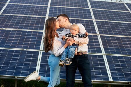Young couple kisses with a baby in her arms on a background of solar panels. Blond kid is looking forward. Slender girl with long hair. Solar energy concept image Foto de archivo - 137589907