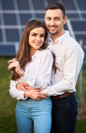Close-up portrait of young and beautiful smiling couple, standing close to each other, holding hands, embracing, wearing white shirts, solar panel on background, concept of happy relationships Foto de archivo - 137589909