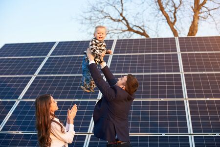 Low angle view of a happy family spending fun time at solar plant, father holding his son above their heads, mother clapping hands Foto de archivo - 137589908