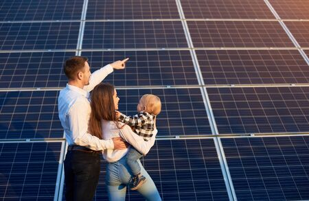 Husband shows his family the solar panels on the background. Blond child in arms of wife. Young family keeps up with the times choosing solar heating Foto de archivo - 138260522