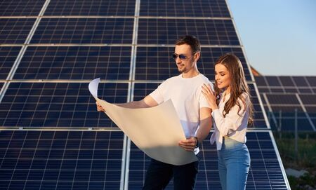 Young couple watching a plan on background of solar panels. Man with a clock in sunglasses, a white T-shirt and jeans familiarizes himself with an important document Foto de archivo - 138266821