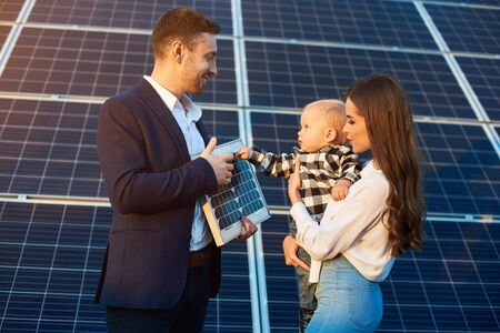 Cheerful kid in his mother arms examines the solar battery that dad holds, against background solar panels. Concept of family warmth and comfort in modern world with continuously advancing technology