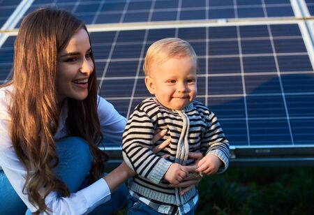 Blonde little child next to her smiling mom looks forward under the suns rays of the sunset against the background of solar panels. Close up. Young beautiful woman holds a baby