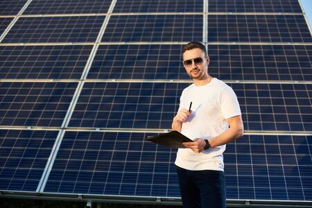 Handsome male with a folder and pen in his hands on a background of solar panels on a warm day. Young man in sunglasses, white T-shirt and jeans is looking at the camera with a smile Foto de archivo - 138267529