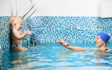 Side view snapshot of mother and son spending fun time in swimming pool, happy woman reaching out her son who is sittting on a silver pipe Foto de archivo - 138285076