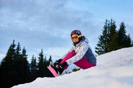 Horizontal snapshot of a young girl freerider, sitting on a slope in the mountains putting her snowboard on, concept of winter sports 版權商用圖片