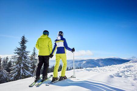 Ein paar Skifahrer, die Händchen am bewaldeten Bergrand halten und die wundervolle Schönheit der Natur im Skigebiet genießen. Winterbergpanoramalandschaft im Hintergrund. Klarer blauer Himmel mit Kopienraum. Rückansicht.