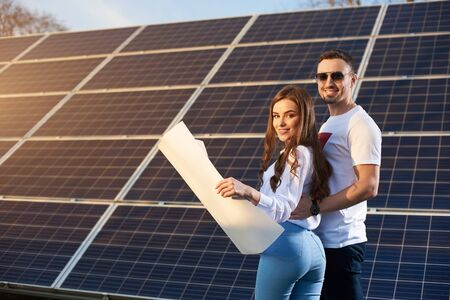 Young smiling sweet couple is standing by a solar module on a sunny day, looking at camera, holding a paper plan wearing similar clothes, copy space, side view 免版税图像