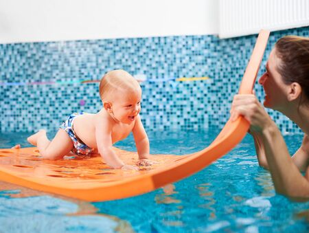 Cheerful baby boy is crawling on a floating mat with holes and playing with a mother. Happy and playful swimming class with instructor