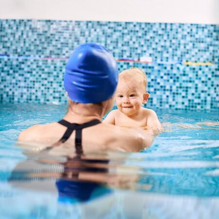 Woman is standing with her back to the camera in pool, pulling a cute little boy so he is trying to swim. Boy is in focus