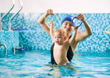Swimming lesson for infants. Mother is training her baby boy in swimming pool using colorful rings, little child is holding rings and floating in water. Concept of early development