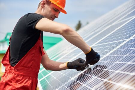 Electrician installing solar panels to save energy. A man is wearing an orange uniform, hard hat, black t-shirt and gloves against the blue sky. Alternative energy sustainable concept