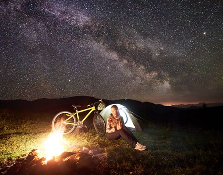 Young woman tourist having a rest at night camping near burning campfire, illuminated tourist tent, mountain bicycle under amazing beautiful evening sky full of stars and Milky way. Astrophotography Banque d'images
