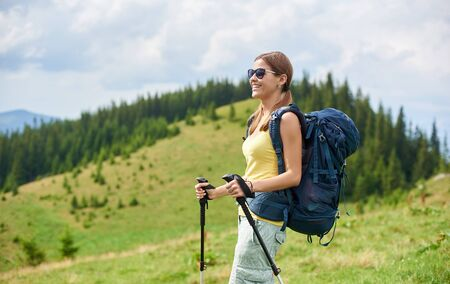Beautiful happy woman backpacker hiking in Carpathian mountain trail, walking on grassy hill, wearing backpack, using trekking sticks, enjoying summer day. Outdoor activity, tourism concept