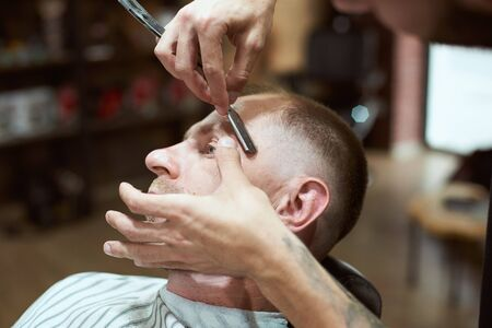 Close-up side view of hair stylists hands shaving his male customers head with a barber shaving razor Stock fotó
