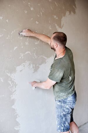 Male worker plastering wall with putty-knife, close up. Fixing wall surface and preparation for painting. Young man with a beard in a T-shirt and shorts smeared with paint