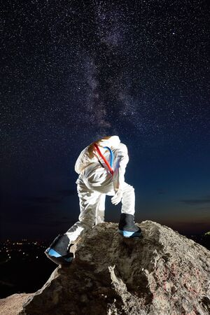 Back view of space traveler reaching top of rocky mountain under mesmerizing night sky with stars, Milky way. Male cosmonaut in space suit exploring new planet. Concept of space travel, cosmonautics Reklamní fotografie