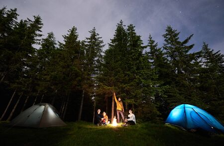 Guy is showing his friends the starry sky over tent city. Tourists are sitting by the fire on background of spruce forest and enjoying evening sky. Outdoor recreation