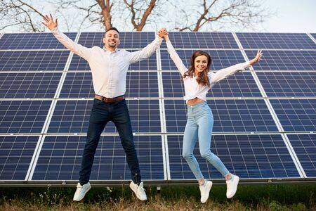 Cheerful young couple jumping together holding hands on the background of solar panels under a blue sky. Young men wearing jeans and white shirts. Solar energy concept image