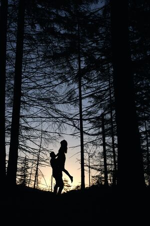 Silhouettes of loving couple posing in evening forest. Wild nature with amazing views, summer sunset, guy holding girl. Nature, love, happyness concept.