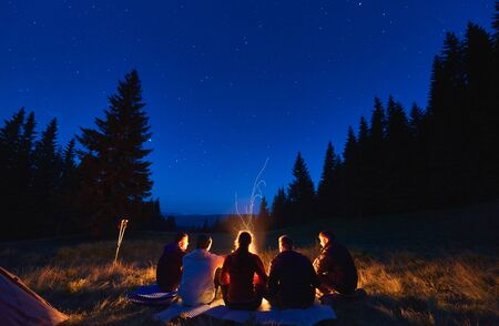 Summer camping under stars. Rear view of group of five hikers, men and woman sitting near bright bonfire, tourist tent under dark night sky with sparkling stars. Concept of tourism, night camping.