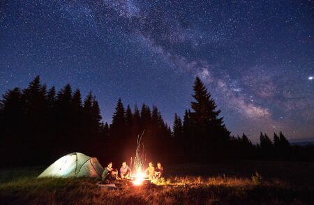 Night camping near bright fire in spruce forest under starry magical sky with milky way. Group of four friends sitting together around campfire, enjoying fresh air near tent. Tourism, camping concept. Imagens
