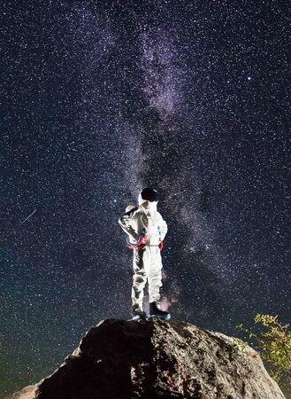 Astronaut standing on top of mountain with mesmerizing night sky with stars on background. Space traveler in space suit keeping hands on waist. Concept of cosmonautics, milky way and space travel.