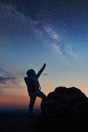 Silhouette of space traveler standing on rocky mountain and pointing at stars, Milky way. Cosmonaut wearing white space suit while looking at fantastic starry sky. Concept of galaxy, human in space