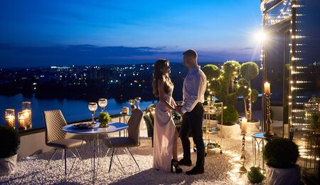 Loving couple holding hands on terrace beautifully decorated for dinner with beautiful views of night city and river. Candles, wine and fruit under blue evening sky create special romantic atmosphere