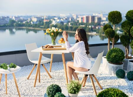 Happy woman in white shirt with bare legs is enjoying sunshine at breakfast on terrace overlooking lake and city in the distance under sunny rays. On table is vase of flowers, coffee and croissants