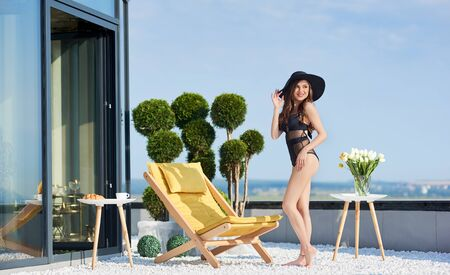 Full length of attractive young woman posing on rooftop terrace with comfortable deckchair, plants and flowers. Charming girl in elegant swimsuit and hat looking aside and smiling. Imagens - 143138269