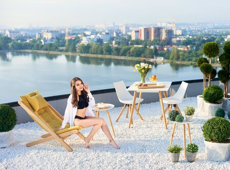 Slender woman in black lingerie and white shirt is having breakfast on balcony with bouquet of tulips overlooking lake and city on sunny day. She is sitting on deckchair at terrace under morning sky. Imagens