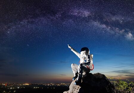 Side view of spaceman pointing at beautiful sky with stars while sitting on top of mountain. Mission specialist astronaut wearing white space suit with helmet. Concept of space travel and night sky. Imagens - 143138271
