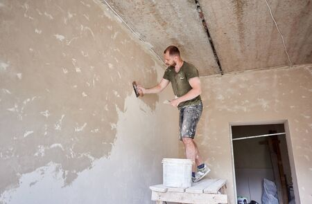 Male builder is standing on a wooden stand and working with a spatula with plaster on the wall in small room. Puttying the walls indoors. A guy with a beard in a t-shirt and jeans is smeared paint