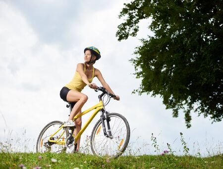 Attractive happy woman cyclist riding on yellow mountain bicycle on a grassy hill, wearing helmet, enjoying summer day in the mountains. Outdoor sport activity, lifestyle concept