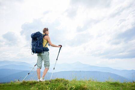 Back view of athlete woman backpacker hiking mountain trail, walking on grassy hill, wearing backpack, using trekking sticks, enjoying summer day in the mountains. Outdoor activity, lifestyle concept