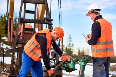 Two oil workers wearing overalls, orange vests, and helmets, working on oil field next to oil pump jack, one is wrenching the pipe, the other making notes. Concept of petroleum industry, collaboration