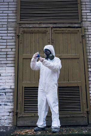 Full length snapshot of ecologist standing in front of old door and observing reaction in glass flask with blue liquid, laboratorial experiment. Scientist wearing white uniform, gloves and gas mask