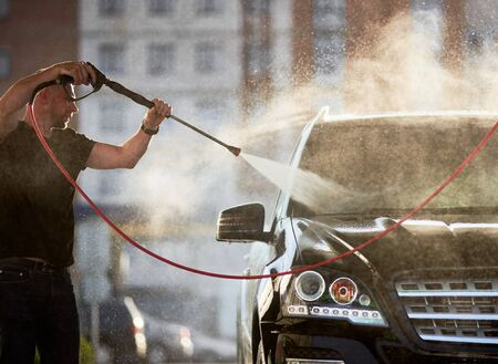 Side view of man cleaning his black car outdoors, water is splashing over the top of the car shining on the sun. 版權商用圖片