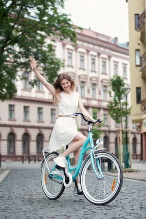 Cheerful young woman with long hair in a light dress rides a blue retro bicycle along the street block of the old city against the background of beautiful architecture. Cycling on a summer day