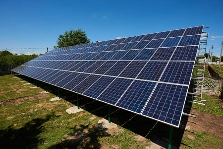 Sideview of huge solar panels installed on outdoors opened space. Modern solution for natural resources saving, using renewable solar energy. Environment friendly, green energy. Warm sunny day. Stockfoto
