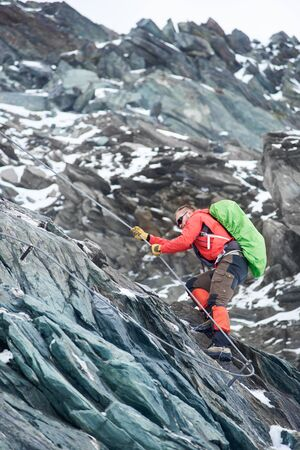 Brave mountaineer in sunglasses holding rope while climbing alpine ridge. Male alpinist with backpack ascending mountain and trying to reach mountaintop. Concept of alpinism and alpine climbing.