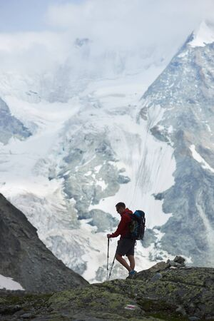 Tourist with backpack walking using trekking sticks, beautiful mountains with snow. Mountain hiking, man reaching peak. Wild nature with amazing views. Sport tourism in Alps.