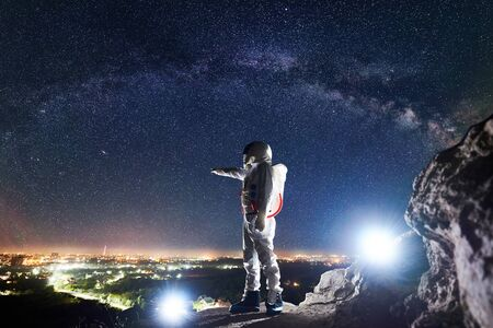 Male spaceman pointing finger at night city in valley while standing on rocky mountain under fantastic night sky with stars and Milky way. Concept of cosmonautics and space traveling.