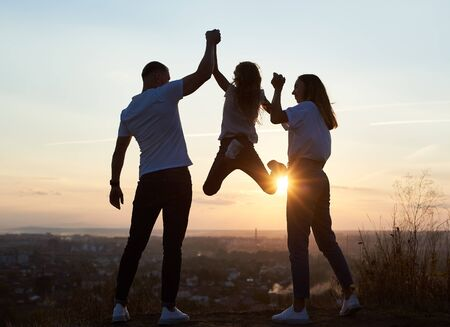 Silhouette di padre madre e figlia che trascorrono una giornata divertente fuori città sulla collina al tramonto con una bellissima vista sulla città, papà e mamma che tengono la ragazza per mano e lei è appesa, vista posteriore Archivio Fotografico