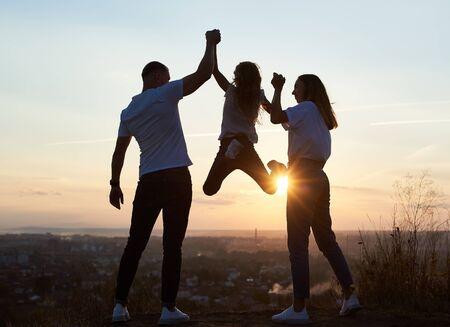 Silhouette von Vater, Mutter und ihrer Tochter, die einen lustigen Tag außerhalb der Stadt auf dem Hügel bei Sonnenuntergang mit einem schönen Blick auf die Stadt verbringen, Vater und Mutter, die Mädchen an den Händen halten und sie hängt, Rückansicht Standard-Bild